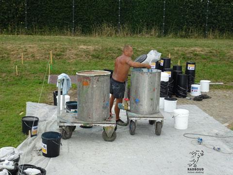 De verf wordt gemengd in de grote vaten.